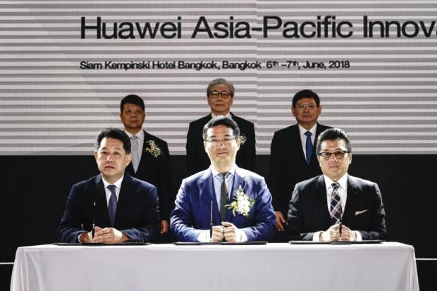 Somkid Jatusripitak (standing, centre) witnessed the MoU signing event, with representatives James Wu (centre), president of Southeast Asia for Huawei Technologies, Narong Sirilertworakul (left), president of National Science and Technology Development Agency, and Pun-Arj Chairatana, director of the National Innovation Agency.