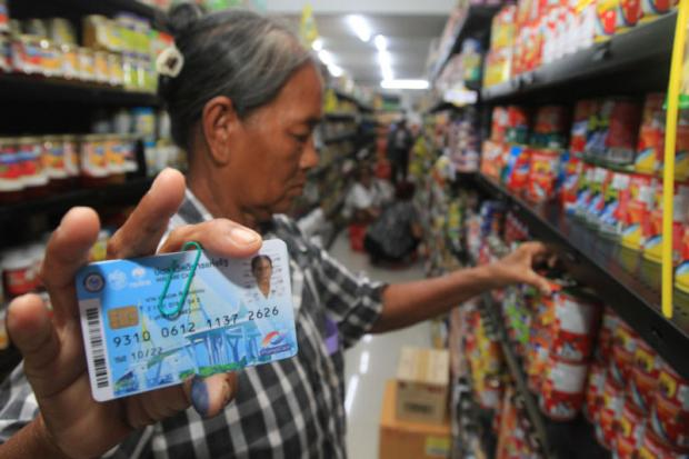 A low-income earner shows her state welfare card before using it to buy food and other necessities.
