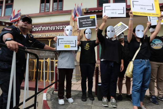 Members of Amnesty International converge outside Bang Khwang Central Prison, hold up placards to denounce the execution of a convict on Monday, the first in almost nine years.Wichan Charoenkiatpakul