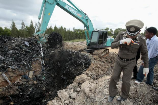 A policeman gags on the stench Tuesday as Industry Ministry officials collect samples of an estimated 60,000 tonnes of electronic waste dumped illegally near a reservoir in Rayong's Pluak Daeng district. (Photo by Patipat Janthong)