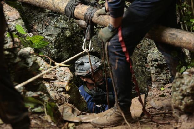 A rescue worker, with help from colleagues, lowers himself into a shaft found on the eastern side of Tham Luang cave complex.(Photo by Patipat Janthong)