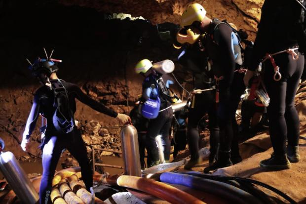Getting ready: Thai rescue team members bring life saving equipment including oxygen tanks into Tham Luang cave in Mae Sai district of Chiang Rai where 12 boys and their football coach have been trapped since June 23. (Thai Navy Seal photo)