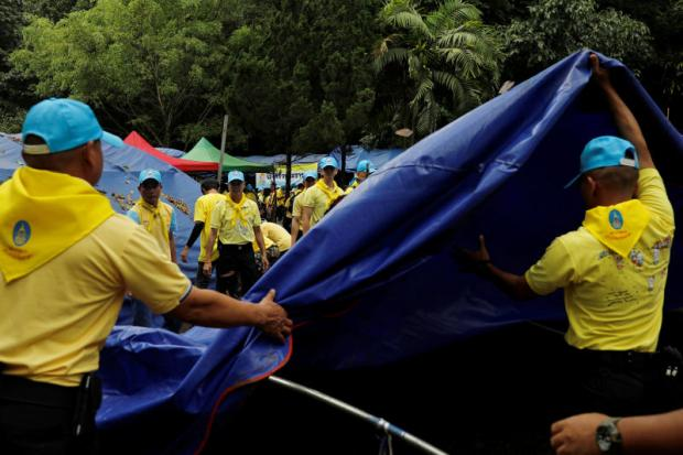 Community vibes: Volunteers remove tents from a rescue campsite for the 12 boys of the 'Moo Paa' football team and their coach, near the Tham Luang cave complex.