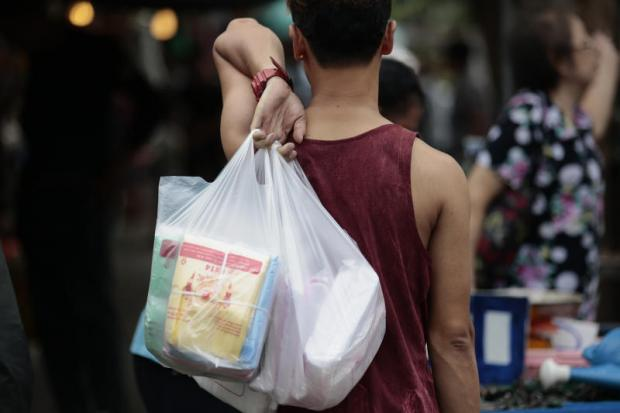 PLASTIC IS FANTASTIC: A shopper heads home with bagfuls of shopping.