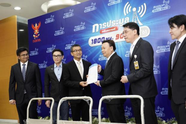 Narupon Rattanasamaharn (third left), DTAC's regulatory head, submitted a bid application for the 1800MHz licence auction to Mr Takorn on Wednesday.