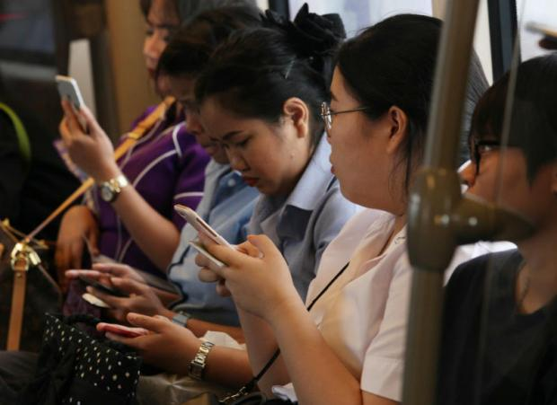 Skytrain passengers on their mobile phones. Mobile virtual network operators have presented a list of amendments for the regulator to consider. APICHIT JINAKUL