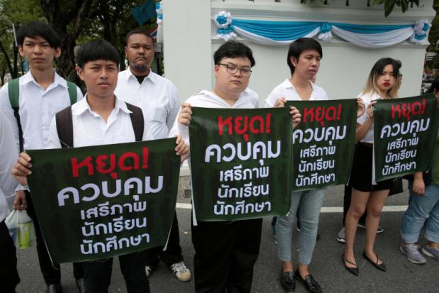 Members of the Student Union of Thailand hold placards with the message 'Stop reining in the rights of students' at the Education Ministry on Friday. (Photo by Chanat Katanyu)