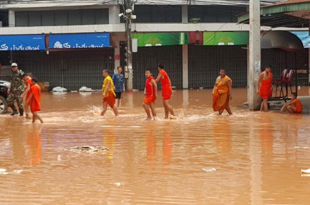 Novice monks wade through a flooded road in Nan's Muang municipality yesterday. Photo: Rarinthon Phetcharoen