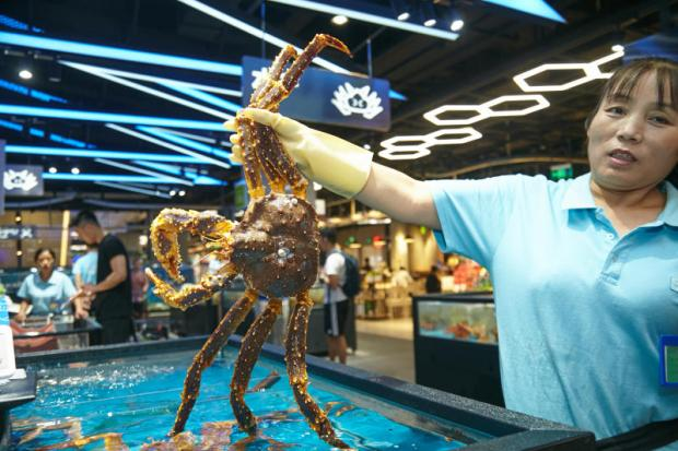 A vendor shows a live lobster. Customers can dine at the supermarket and take care of the bill using Alipay.
