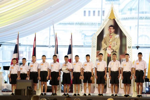 Twelve 'Wild Boars' footballers stand before a portrait of His Majesty the King as one reads a message of thanks to everyone involved in the Tham Luang rescue operation between June 23 and July 10 in Chiang Rai. They also pledged to dedicate themselves to doing good deeds. Patipat Janthong