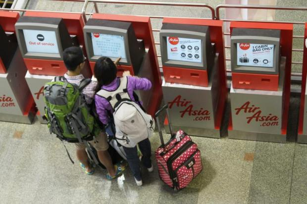 Thai AirAsia passengers check in at Don Mueang airport. The carrier wants permission to use a facial recognition system.