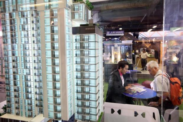 A condominium sales booth at a housing fair. The central bank has adjusted its proposed housing loan curbs.