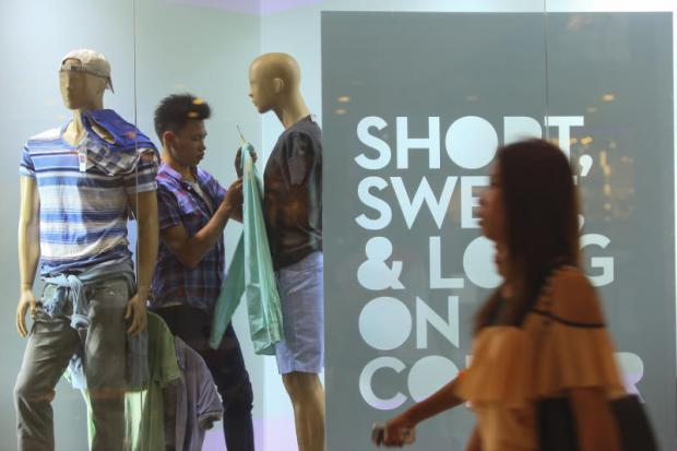 A man changes clothes for mannequins at a shopping mall.(Photo by Pattararpong Chatpattarasill)