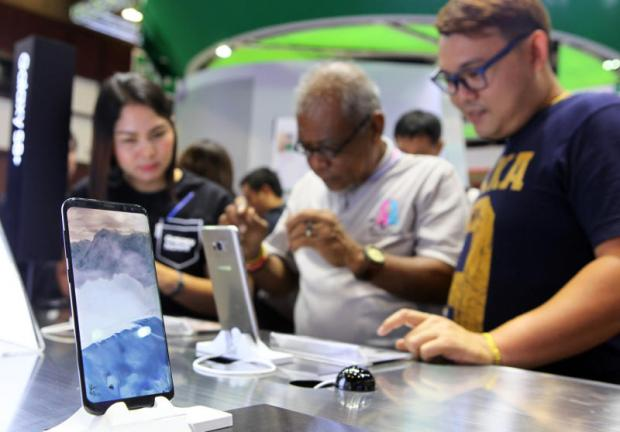 Visitors check out smartphones at a mobile fair. The adoption of 5G is expected to create exponentially better network services for all sectors.TAWATCHAI KEMGUMNERD