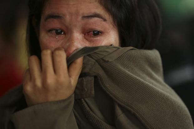 Cambodian workers cry after being arrested by immigration police.