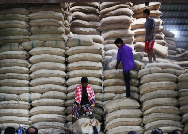 Workers unload sacks of rice in a warehouse in Nakhon Pathom. TAWATCHAI KEMGUMNERD