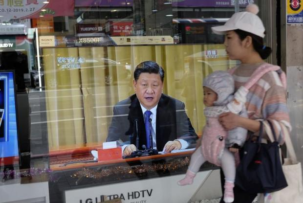 A mother carries her child past a television in New Taipei City on Jan 2 showing China's President Xi Jinping making a speech about Taiwan's 'inevitable' unification with the mainland. (AFP photo)
