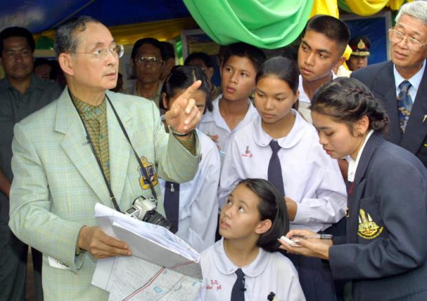In this file photo, His Majesty the late King Bhumibol makes a gesture as he explains the importance of soil and water to students of Klai Kang Won School in Hua Hin while visiting Khao Tao reservoir in Prachuap Khiri Khan.Bangkok Post photo