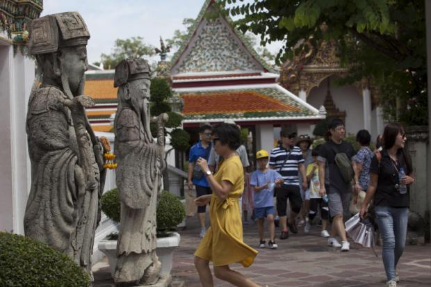 Foreign tourists visit Wat Pho in Bangkok. Atta is bullish on Chinese tourists returning. (Photo by Pawat Laopaisarntaksin)