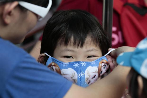 A Malaysian girl is seen with a face mask on Friday as her family visits the Erawan Shrine in Bangkok. (Photo by Patipat Janthong)