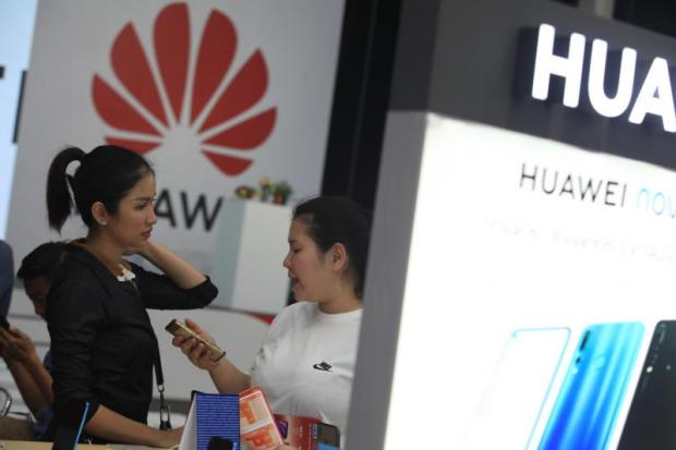 A Huawei saleswoman helps a visitor at the company's booth during Thailand Mobile Expo 2019 at Bitec.SOMCHAI POOMLARD