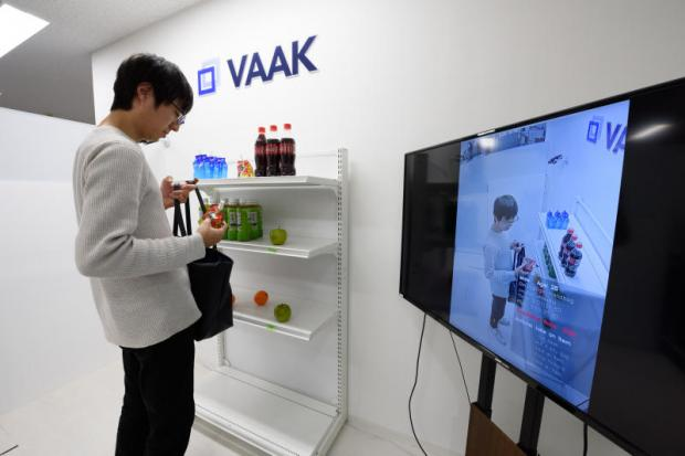 A screen displays a Vaak employee handling a product in a mock store while demonstrating the company's shoplifting-detection system in Tokyo. (Bloomberg photo)