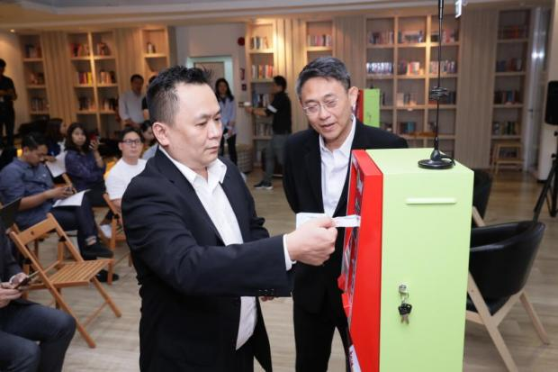 Mr Chookiat demonstrates how to refill credits for prepaid mobile service via a new kiosk.
