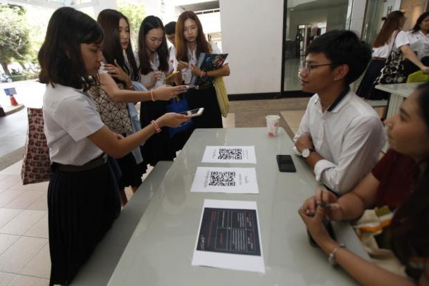 Chulalongkorn University students use their mobile phones to scan bar codes to sign an online petition pressing for the impeachment of the poll commissioners due to alleged mistakes in organising the general election.(Photo by Varuth Hirunyatheb)