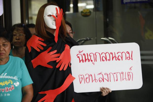 A masked activist wearing a 'being groped' robe holds a placard at the Department of Local Administration reading 'I'm sexually assaulted at Songkran', as she calls for a crackdown on molestation during the festival.(Photo by Varuth Hirunyatheb)