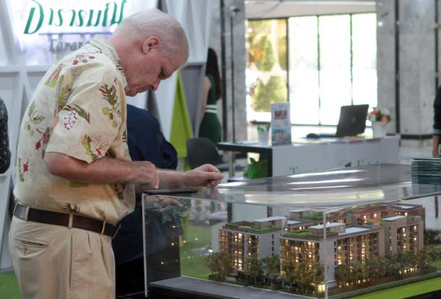 A man looks at a model of a low-rise condominium at a housing fair.TAWATCHAI KEMGUMNERD