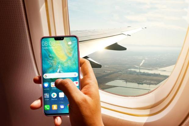 A man holds a smartphone on an aeroplane. Recent market research found Oppo, Huawei and Vivo thriving in Thailand.