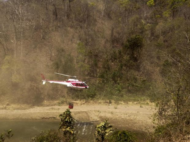 A helicopter airlifts water to fight bush fires in Salawin National Park in Mae Hong Son. Helicopters have made over 100 trips to drop water.Photo courtesy of the Department of National Parks, Wildlife And Plant Conservation