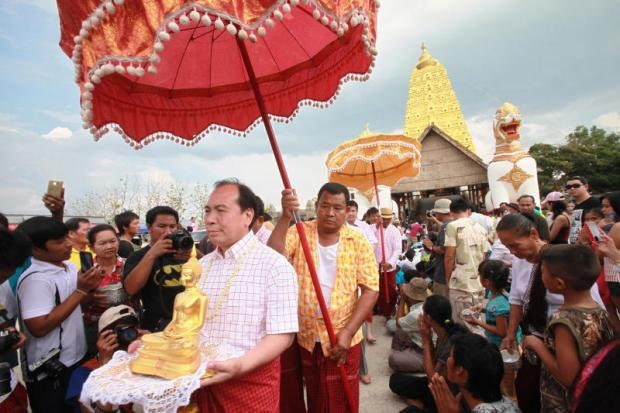 The highly respected seated Buddha image is taken from the temple hall to be blessed by villagers. Pornprom Satrabhaya