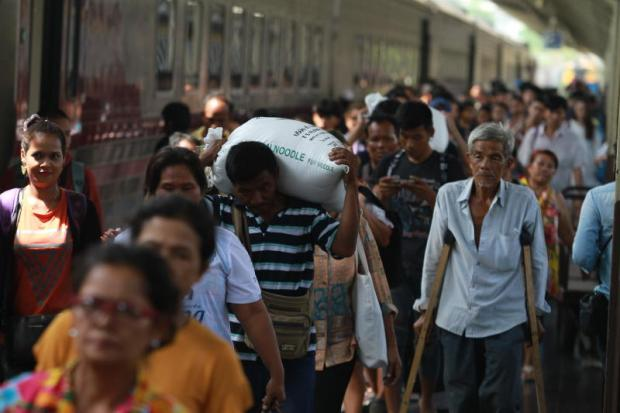 A man is seen carrying what appears to be a sack of rice as he and dozens of others arrive at Hua Lamphong railway station yesterday after arriving back in Bangkok from the provinces following the Songkran holiday.Somchai Poomlard