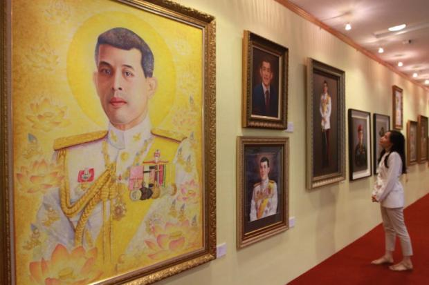A visitor looks at paintings of His Majesty the King at an exhibition dedicated to the monarch. The event, which features more than 150 works by more than 100 renowned artists, will run until May 26 at Seacon Square Srinakarin in the capital.(Photo by Somchai Poomlard)