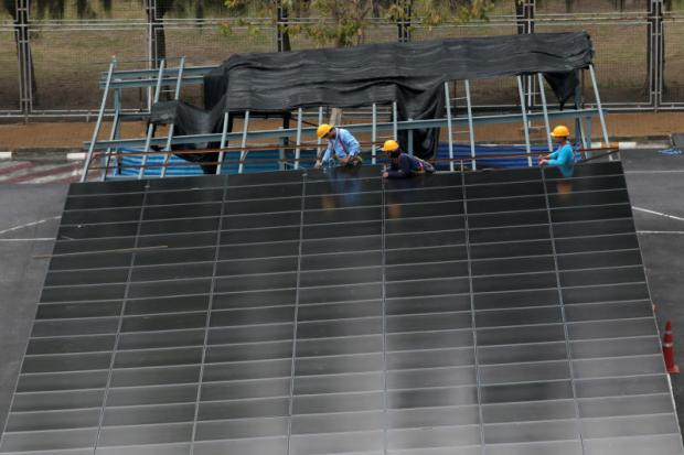 Workers are installing solar panels as roofs in parking lots. Thailand needs recycling facilities to support widespread use of solar panels. Chanat Katanyu