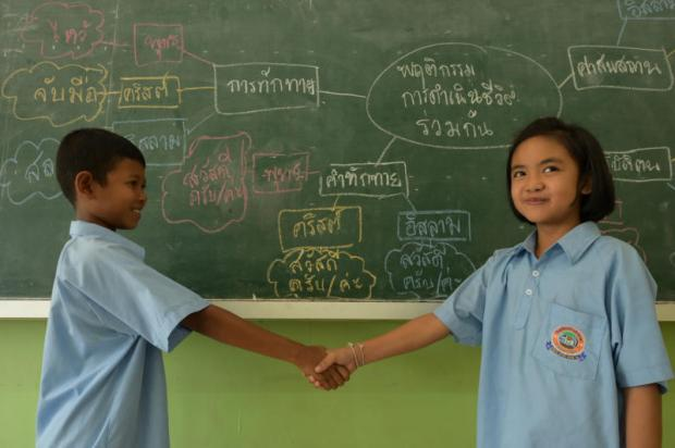 Students in Grade 3 at Baan Ta Art School shake hands as they learn about global citizenship and respecting diversity during a social studies class. Global citizenship, an essential 21st-century skill for young people, refers to having a sense that you belong to a broader community, with more interconnectedness between local people and the wider population.