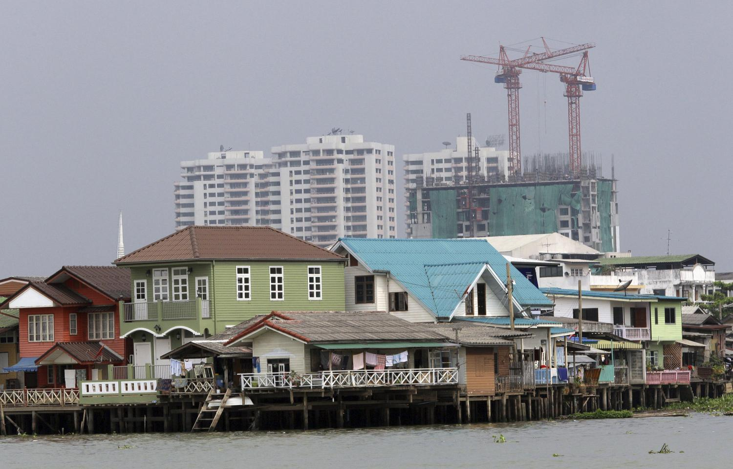 No place like home: Homes pop up along the Chao Phraya River in front of a construction site in Bangkok. The capital is among the mega coastal cities projected by a UN panel to become totally or partially under water as global warming boosts sea levels.