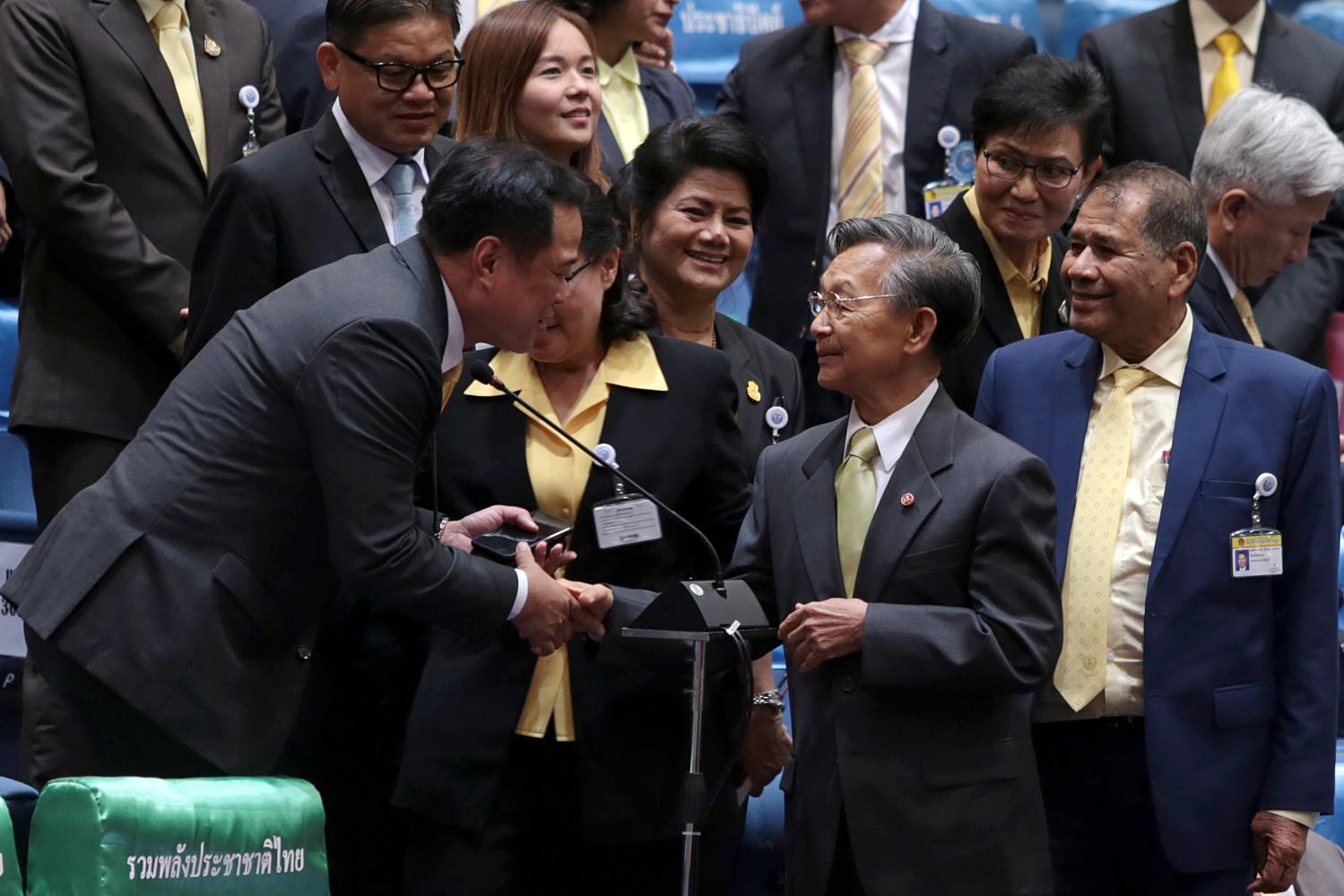 Bhumjaithai Party leader Anutin Charnvirakul, left, congratulates the Democrat Party's chief adviser Chuan Leekpai, centre, after the latter was voted House Speaker on May 25.  CHANAT KATANYU