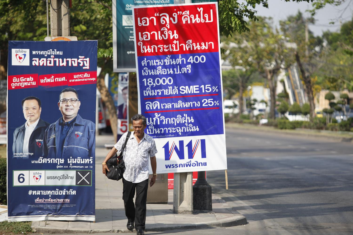 A man walks past a signboard listing Pheu Thai Party policies during the election campaign in March.(Photo by Varuth Hirunyathep)