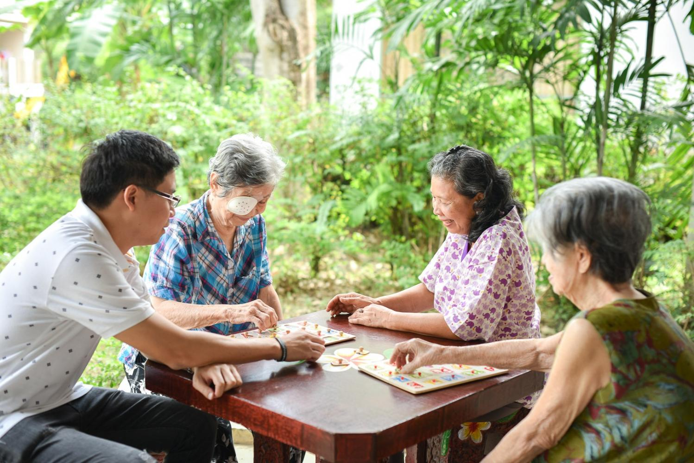 Staff at Navasri Nursing Home help elderly residents play games.