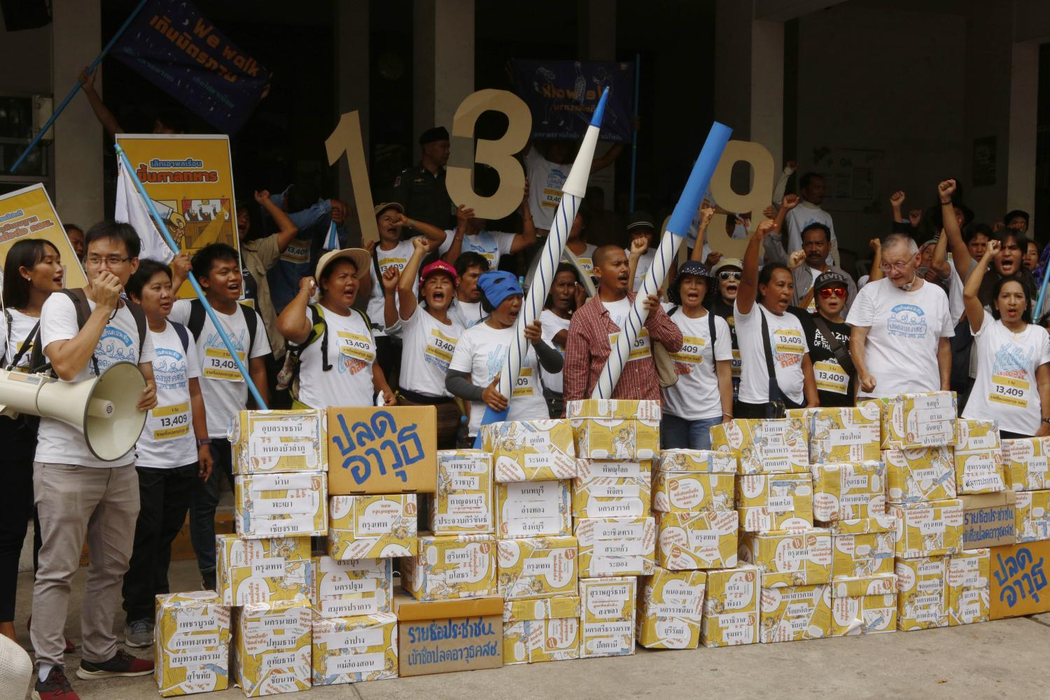 Civic groups stand behind boxes containing signatures backing a draft bill seeking to repeal the military regime's orders and announcements.Pornprom Satrabhaya