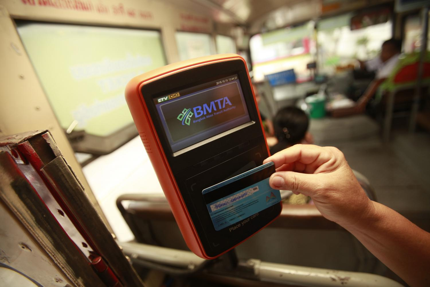 A passenger pays a bus fare using a state welfare card. The new finance minister will decide whether to introduce further measures to help low-income earners.PORNPROM SATRABHAYA