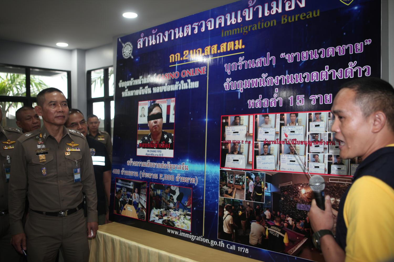 Acting Immigration Bureau chief Sompong Chingduang (left) listens during a press briefing about the arrest of transnational criminal suspects and illegal foreign masseurs at his headquarters on Friday.(Photo by Apichart Jinakul)