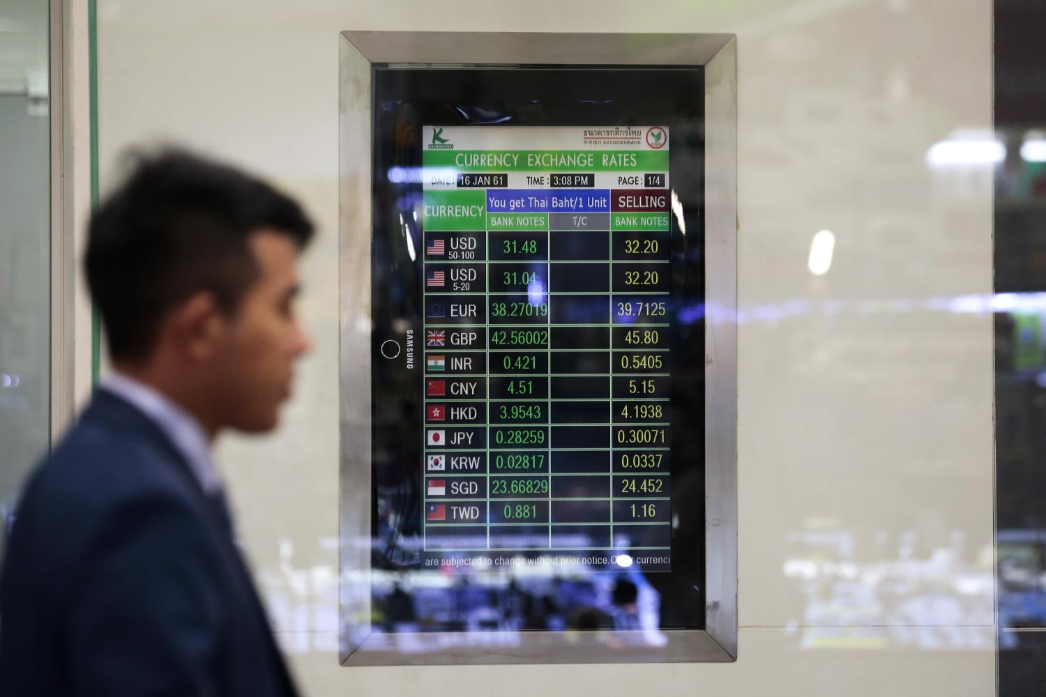 A man walks past a bank's currency exchange board in the capital. (Photo by Patipat Janthong)