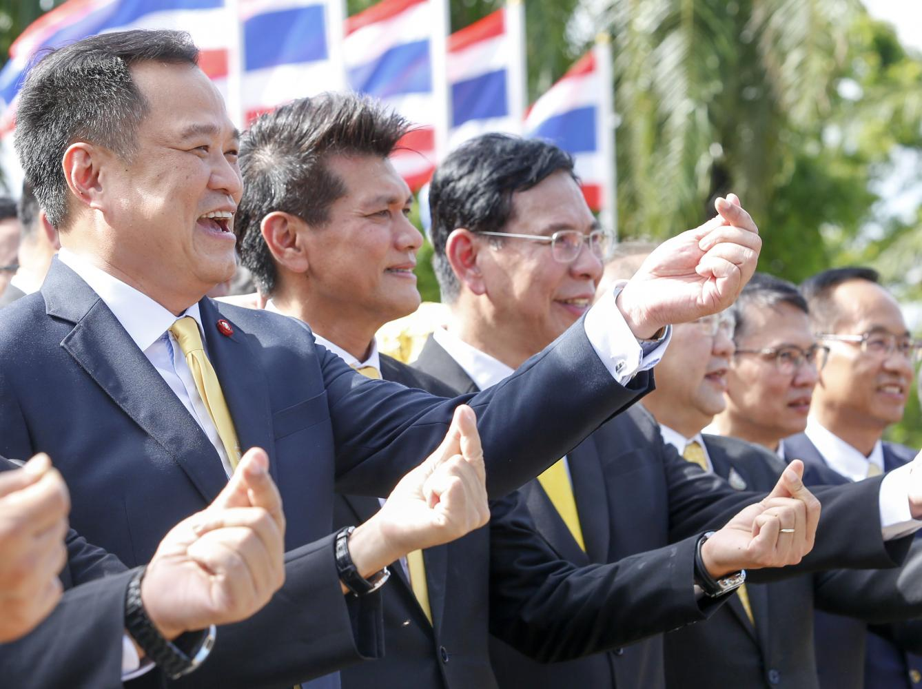 Public Health Minister Anutin Charnvirakul, left, and his deputy, Satit Pitutacha, second left, make a small heart gesture as they report on their first day of work on Thursday. (Photo by Pattarapong Chatpattarasill)