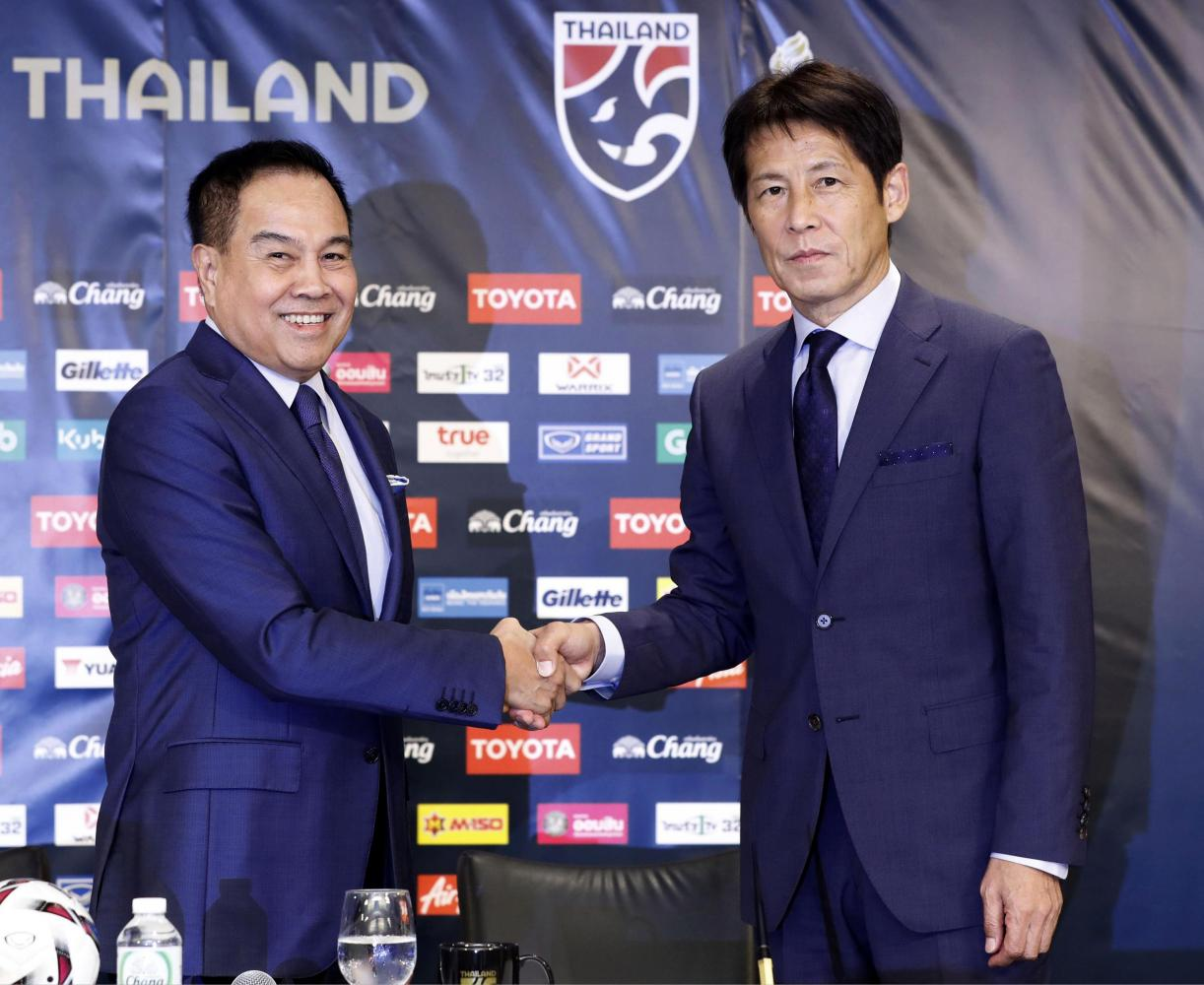New Thailand coach Akira Nishino (right) and Thai football chief Somyot Poompunmuang shake hands during the contract signing ceremony in Tokyo on Friday. (AP photo)