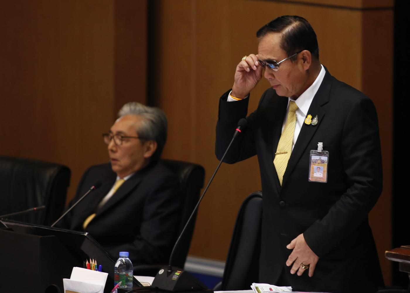 Prime Minister Prayut Chan-o-cha, right, speaks during the government policy debate in parliament last week. His government's manifesto does not address life-threatening problems faced by the Thai economy, says Bangkok Post columnist Chartchai Parasuk. PATTARAPONG CHATPATTARASILL