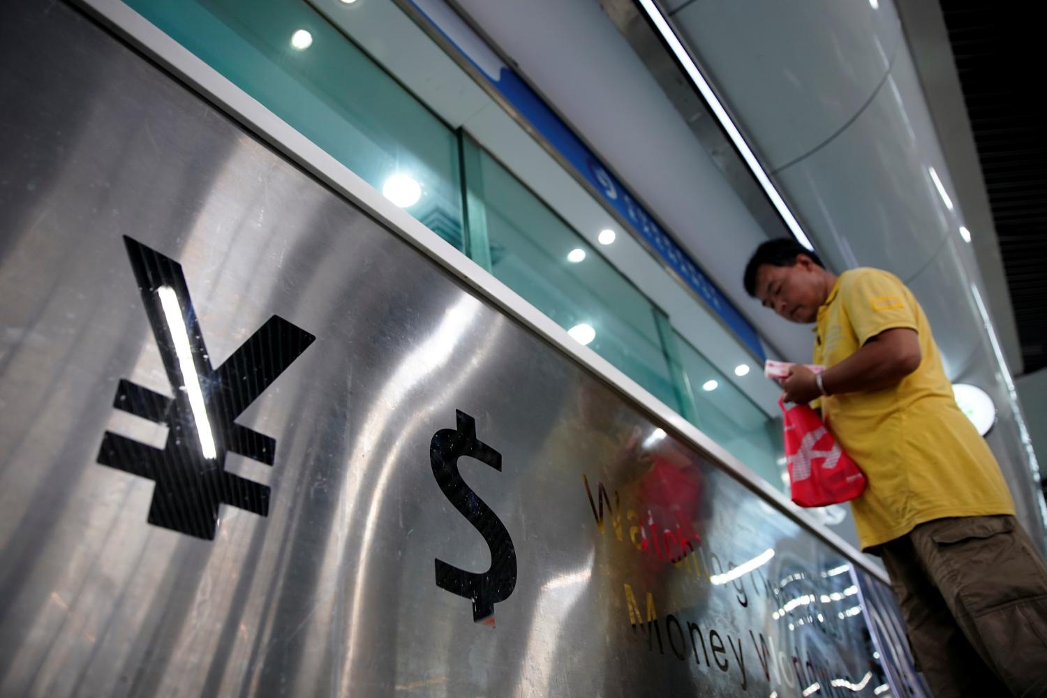 A currency exchange shop in Shanghai. The yuan may fall further still, say analysts. (Reuters photo)