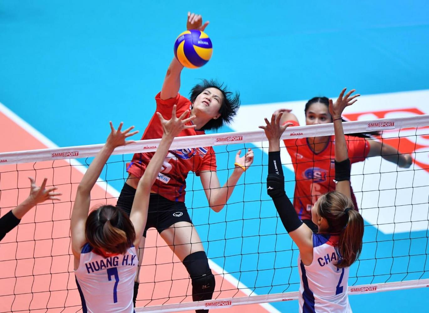 Thailand's Pleumjit Thinkaow spikes the ball during the Pool C match against Taiwan. Onuma Sittirak is on her left.